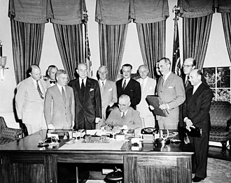 Portugal during World War II - President Truman signing the North Atlantic Treaty with Portuguese Ambassador Teotónio Pereira standing behind.