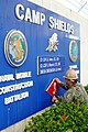 U.S. Navy Construction Electrician Anthony Martinez changes the welcome sign at Camp Shields in Okinawa, Japan after a change of charge ceremony between Naval Mobile Construction Battalion (NMCB) 3 and NMCB-5 130818-N-SD120-004.jpg