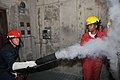 U.S. Navy Seaman Recruit Jesus Fierro, observed by Machinist's Mate 1st Class Shakeysha Fludd, sprays CO2 extinguishing agent on an electrical panel during a simulated Class Charlie electrical fire, in the USS 120705-N-IK959-933.jpg