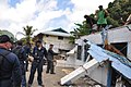U.S. Sailors, assigned to the guided missile frigate USS Ingraham (FFG 61), and American Samoan civilians prepare to pull down the remaining part of a roof from a house during cleanup efforts in Pago Pago 091003-F-LX971-348.jpg
