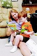Une femme blonde assise faisant la lecture à un jeune garçon roux à lunettes assis sur sa jambe