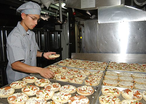 US Navy 050313-N-2198V-011 Culinary Specialist 3rd Class Robert Diaz from the Republic of Puerto Rico prepares pizza for the crew
