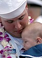 US Navy 050908-N-3019M-006 Seaman Chad Herod, assigned to the guided missile destroyer USS Paul Hamilton (DDG 60), holds his son after returning to Pearl Harbor.jpg