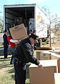 US Navy 051213-N-9274T-002 U.S. Navy Storekeeper 1st Class Luis Vera, assigned to Naval Air Station Joint Reserve Base New Orleans, opens boxes filled with coolers brought to New Orleans by The American Red Cross.jpg