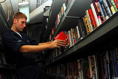 US Navy 070224-N-9928E-020 Airman Rick Mowry places books in back on shelves in the ship's library aboard Nimitz-class aircraft carrier USS John C. Stennis (CVN 74).jpg
