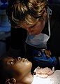 US Navy 070904-N-6278K-214 Canadian Forces Cpl. Julie Belisle, a dental technician attached to the Military Sealift Command hospital ship USNS Comfort (T-AH 20), calms a patient before a tooth extraction at Hôpital.jpg