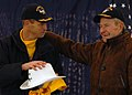 US Navy 080125-N-8544C-137 Capt. Kevin O'Flaherty, commanding officer of Precommissioning Unit (PCU) George H.W. Bush (CVN 77), presents former President George H.W. Bush with a yellow shooter's jersey and a specially made cowb.jpg