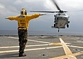 US Navy 080212-N-5067K-443 Aviation Boatswain's Mate (Helicopters) Airman, Kevin A. Bourne directs an MH-60S Seahawk during deck landing qualifications on the flight deck aboard the amphibious transport dock USS Juneau (LPD 10).jpg