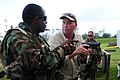 US Navy 081014-N-0411D-036 Former Seabee Chief Richard Rader, right, describes to Boatswain's Mate 1st Class Kenneth Scales how properly gripping a handgun can affect marksmanship during tactical handgun marksmanship training.jpg