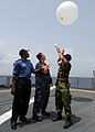 US Navy 100401-N-6138K-646 Nigerian navy Cmdr. Godffrey Kwetishe, left, Aerographer's Mate 2nd Class Cory Clare, from Apopka, Fla., and Lt. Brandon Le, from Monterey, Calif., launch a weather balloon.jpg