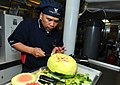 US Navy 101208-N-6632S-018 Culinary Specialist 2nd Class Rudy L. Tabayoyong, from the S-2 Division of the supply department, carves a watermelon fo.jpg