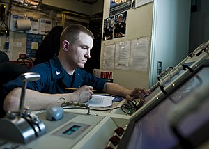 US Navy 120118-N-FI736-100 Aviation Machinist's Mate 3rd Class Leo Barth records data from a test run on the engine of a F-A-18C Hornet aboard the.jpg