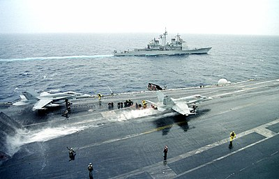 US Navy 990225-N-9693M-005 The USS Philippine Sea (CG 58) steams off the port side of the USS Enterprise, while an F-A-18C.jpg