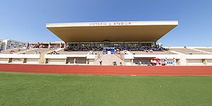 "The stand of a football stadium, appearing to be made of concrete, in the daytime. The centre section of the stand is covered by a roof. On the front edge of the roof, the letters ""VICTORIA STADIUM"" can be seen."
