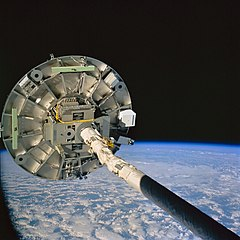 The Wake Shield Facility is deployed  by the Space Shuttle's robotic arm. NASA image.
