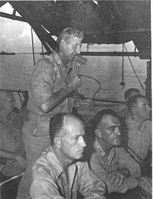 Man standing on deck of ship talking to a microphone. Two other men are seated at a desk in the foreground.