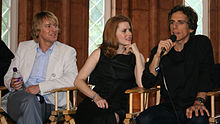 Casual photo of a young woman sitting between two men in director chairs. The woman is wearing a black, sleeveless dress and is intently listening to one of the men, Ben Stiller, talk into a microphone.