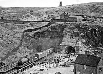 Woodhead Tunnel - Photograph from 1953 showing the western portals of the Woodhead tunnels. To the left, a train emerges from one of the original tunnels, whilst tunnel 3 is under construction to the right.