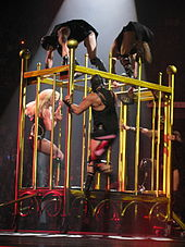 The right profile of a female blond performer. She is moving inside a giant golden cage, she is wearing a black corset with diamonds and fishnet stockings. Four leather-clad men seem to be chasing her.