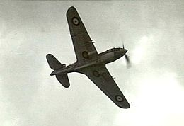 Underside of single-engined monoplane in flight, with twin machine guns on each wing