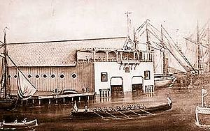 Detroit Boat Club - The 10-oared barge Henrietta from the Teutonia Boat Club passes the Detroit Boat Club at the foot of Jos. Campau in 1878. The DBC had not yet moved to Belle Isle.