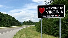 "A large rectangular metal sign, mostly black, with the words ""Welcome To Virginia"" and ""Virginia is for lovers"" with a red heart symbol on the left."