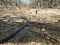 A woman walks along the creek at Rock Creek Crossing in Council Grove, KS (f917e2aff03b44a18e4f7a057dc597d7).JPG