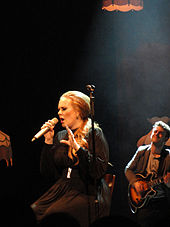 A blonde woman is sitting, while performing and holding her microphone in her hand.