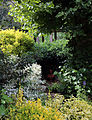 An obscured terracotta feature in shrubs Gibberd Garden Essex England.JPG