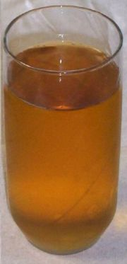 A glass of clear apple juice, from which pectin and starch have been removed.