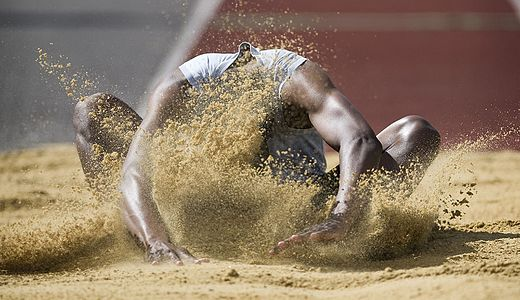 Army long jump athlete lands in the sand.