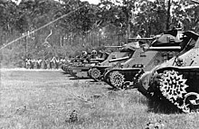 Black and white photo of a row of tanks of different designs. A line of people is visible in the background, standing in front of tall trees.
