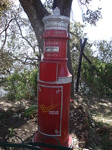 Tall, round red mailbox with decorative crown on top