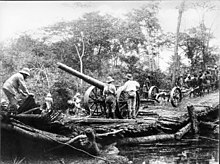 An impressive artillery piece is pulled across a small stream. Men in African colonial-style dress stand around.