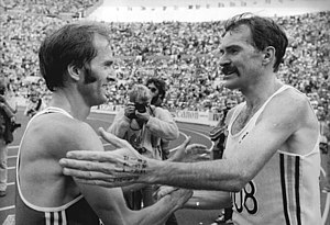 1983 World Championships in Athletics - Marathon bronze medallist and reigning Olympic champion Waldemar Cierpinski (DDR) celebrates with gold medal winner Robert de Castella (AUS).