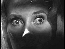Black and white close up image of a woman's eyes, wide in fear or shock.