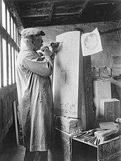 een man die een esdoornblad op een grafsteen snijdt, in een werkplaats, met een hamer en een beitel.