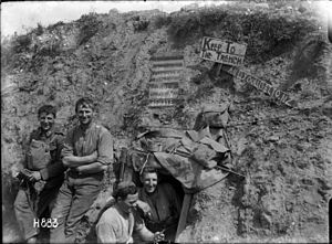A black and white photograph of a group of men in military uniform in a trench in front of a sign which reads: The Cannibals Paradise Supply Den Beware