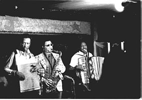 Chenier Brothers performing at Jay's Lounge and Cockpit, Cankton, Louisiana, Mardi Gras, 1975 Clifton Chenier on accordion, brother Cleveland on washboard and John Hart on tenor saxophone.