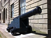A cannon is positioned next to a brick wall