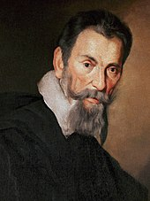 Head of a heavily bearded short-haired man with a serious expression, leaning slightly forward and facing semi-right, although his eyes look straight ahead. A white collar over a dark coat or cloak is also visible.