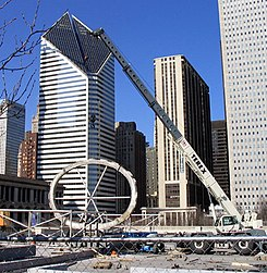 A crane lifts a large, oval-shaped ring in front of several large buildings
