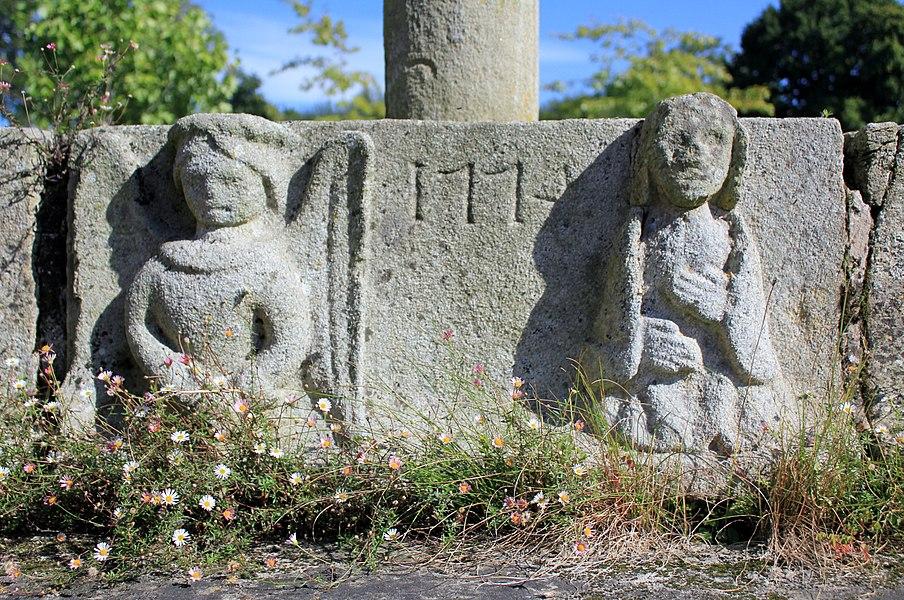 Croix de cimetière de Saint-Allouestre, Morbihan, France. Vue générale du gradin avec l'ange de l'annonciation à gauche, la date 1774 au centre, et la vierge à droite.