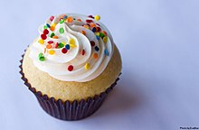 A photograph of a cupcake with white frosting and multicoloured sprinkles.