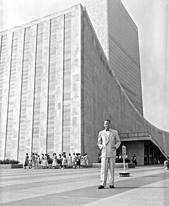 UN Secretary General Dag Hammarskjold in front of the United Nations Headquarters building, completed in 1952 Dag Hammarskjold outside the UN building.jpg