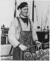 Denmark. Fisherman Holger Hansen, (of) the Skaw (Skagen), Denmark, ties shrimp nets. The big decorative green glass... - NARA - 541665.tif