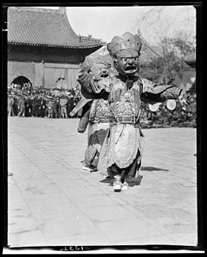 Two dancers in masks and costumes perform