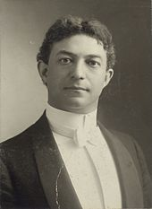 Black and white portrait of a white man with dark hair. He is wearing a tuxedo with a white bow tie.