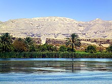 In the foreground the Nile, in the middle ground, luxurious plants and palms trees, in the background the barren hills of the desert