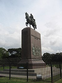 Behind a black iron fence stands a tall, rectangular stone plinth topped by a bronze equestrian statue